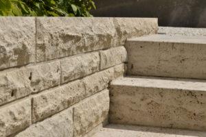 Mit Schichtbossen ausgestattet präsentiert sich das Verblendmauerwerk aus Bauhaus Travertin eines Einfamilienhauses im rheinland-pfälzischen Mendig. Auch die 15 umfassenden Blockstufen entsprechen demselben Gestein, dessen Oberfläche hierfür mit Schliff C 120 bearbeitet wurde.